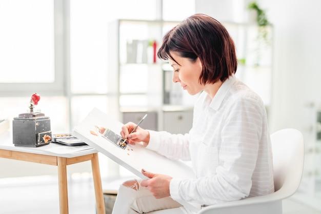 Femme artiste dessin à l'aquarelle sur boîte à musique vintage papier toile blanche de la nature en studio d'art