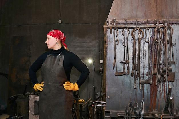 Femme artiste métal forgeron dans son atelier à côté d'un four de forge et d'outils