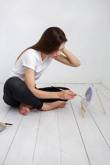 Femme artiste peignant une image sur le sol dans une pièce lumineuse.