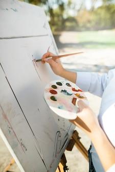 Femme artiste peignant en plein air