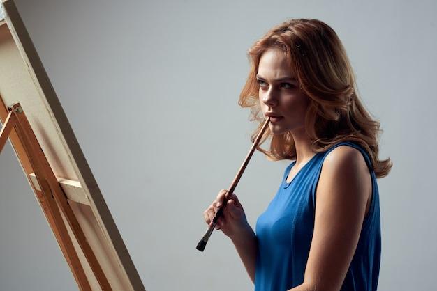 Femme artiste peint une image sur toile avec un chevalet