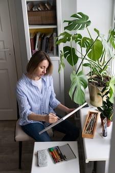 Femme artiste peint une image sur toile, fait des croquis au crayon, assise à la maison pendant le verrouillage