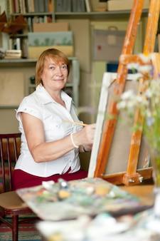 Femme artiste peint une image sur toile