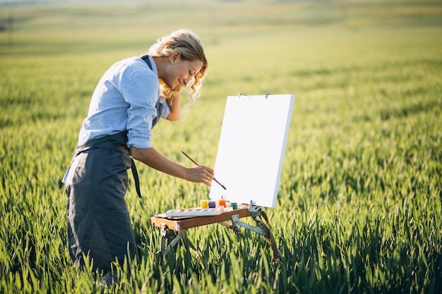 Femme artiste peinture avec des peintures à l'huile dans un champ