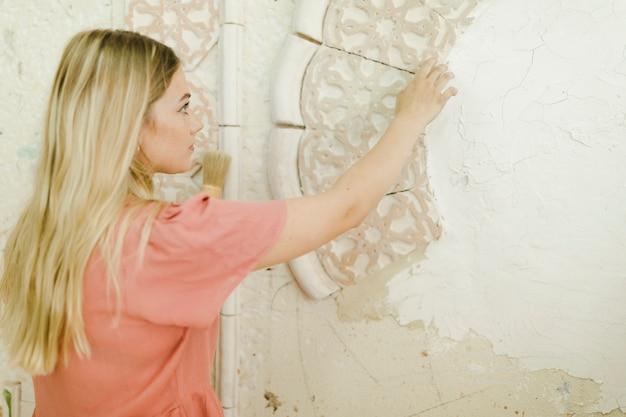 Femme artiste regardant un dessin sculpté sur un mur