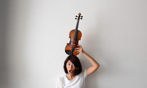 Femme ascenseur violon mis sur sa tête, visage effronté, modèle posant avec instrument acoustique, sentiment de bonheur