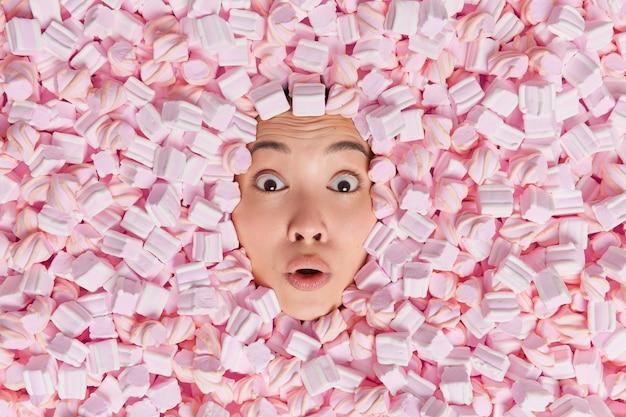 Une femme asiatique abasourdie passe la tête à travers des guimauves roses et blanches, les yeux écarquillés, découvre la quantité de calories qu'elle a consommée