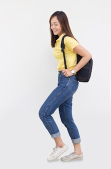 Femme asiatique adolescente avec école bagwalking sur fond blanc avec tenue décontractée