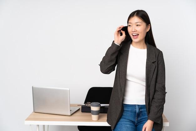 Femme asiatique d'affaires dans son lieu de travail sur le mur blanc, tenir une conversation avec le téléphone mobile