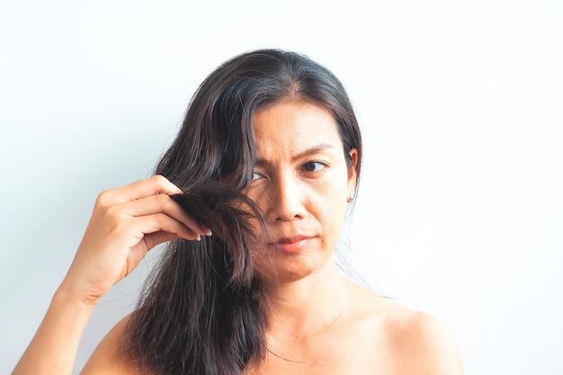 Femme asiatique d'âge moyen inquiète pour les cheveux abîmés. concept santé et beauté