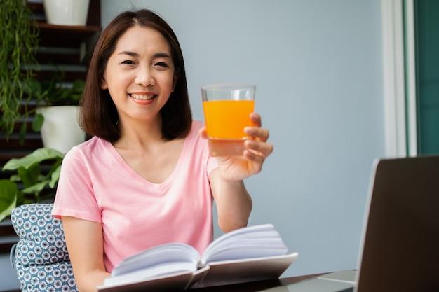 Femme asiatique d'âge moyen lisant un livre et tenant un verre de jus d'orange dans son balcon
