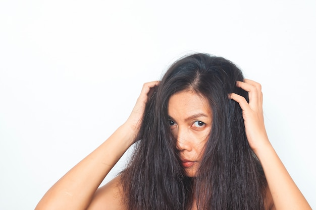Femme asiatique d'âge moyen en regardant la caméra inquiète pour les cheveux abîmés. concept santé et beauté