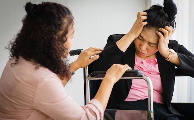Une femme asiatique âgée d'âge moyen prend soin et soutient les femmes souffrant de maux de tête avec des attaques d'avc en fauteuil roulant. concept de problème de cerveau et de tête.