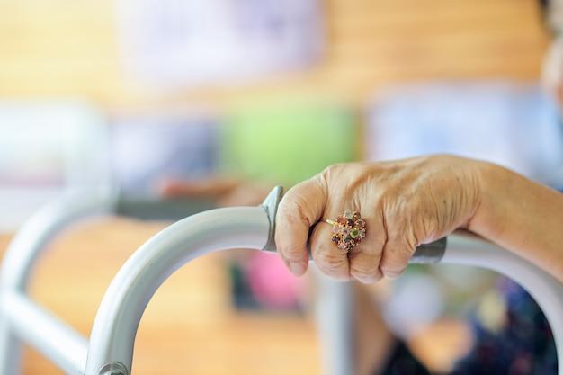 Femme asiatique âgée à l'aide d'un déambulateur au restaurant