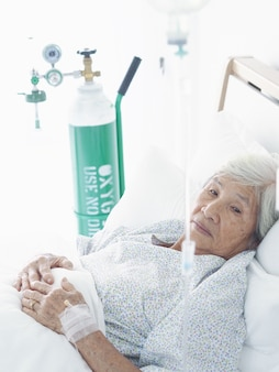 Femme asiatique âgée, couchée sur un lit dans une chambre d'hôpital.