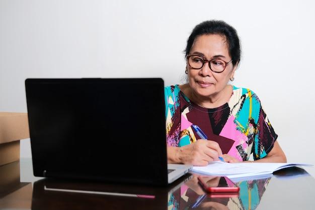 Une femme asiatique âgée écrit une note dans un livre tout en regardant son ordinateur portable
