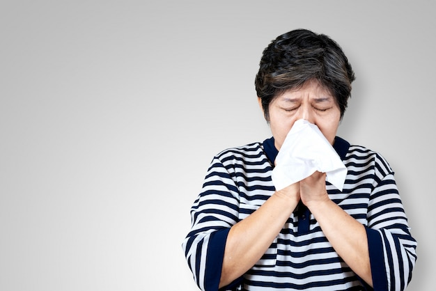 Une femme asiatique âgée a la grippe et éternue à cause d'un problème de virus saisonnier