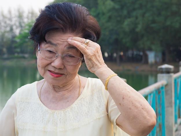 La femme asiatique âgée portait des lunettes. elle n'était pas à l'aise avec des maux de tête.