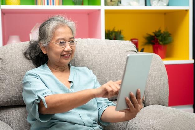Femme asiatique âgée portant des lunettes et se relaxant à la maison sur un canapé et utilisant une tablette pour lire les actualités