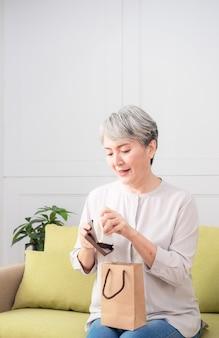 Femme asiatique âgée recevant un cadeau de collier de perles.
