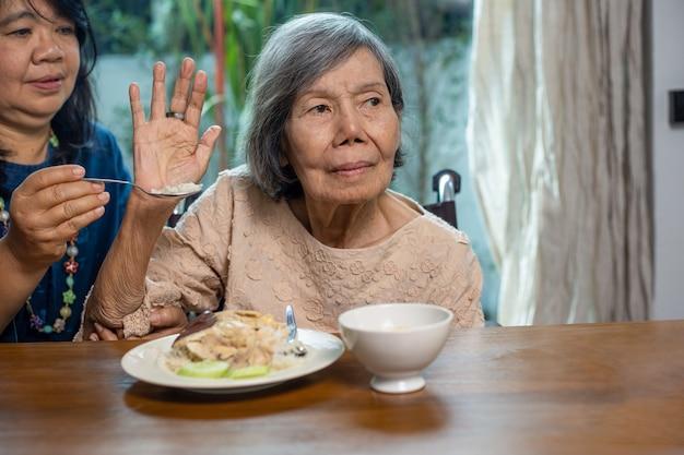 Une femme asiatique âgée s'ennuie avec de la nourriture.