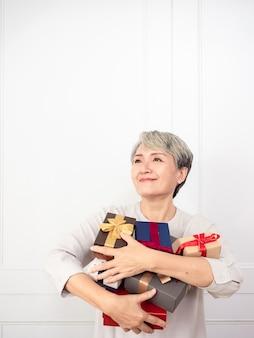 Femme asiatique âgée tenant une monture de coffrets cadeaux, profitant de nombreux meilleurs cadeaux.