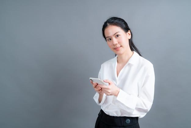 Femme asiatique à l'aide d'applications de téléphonie mobile, appréciant la communication en ligne à distance dans un réseau social ou des achats isolés