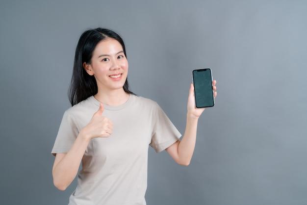 Femme asiatique à l'aide d'applications de téléphonie mobile, profitant de la communication en ligne à distance dans un réseau social ou des achats isolés sur un mur gris