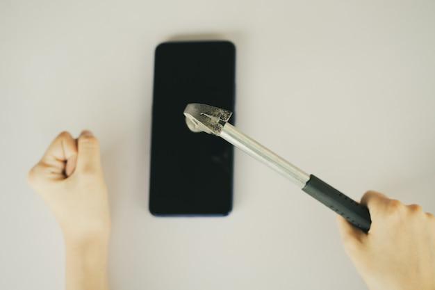 Femme asiatique à l'aide d'un marteau pour casser son smartphone
