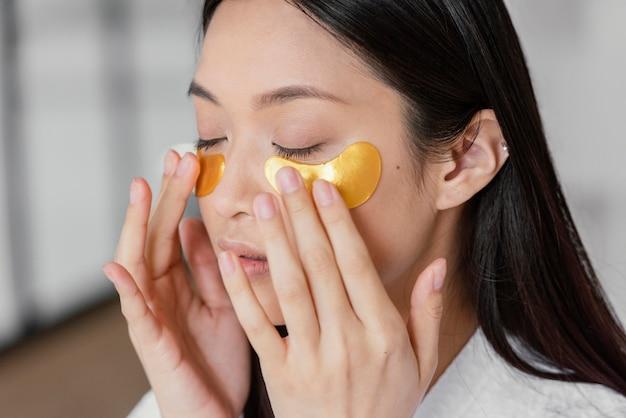Femme asiatique à l'aide de patchs oculaires