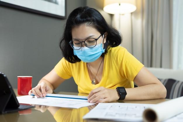 Femme asiatique à l'aide d'une règle d'échelle pour la mesure sur ses plans pendant la quarantaine dans le coronavirus pandémique. architecte d'intérieur jeune femme en chemise jaune, masque chirurgical bleu, travail à domicile.