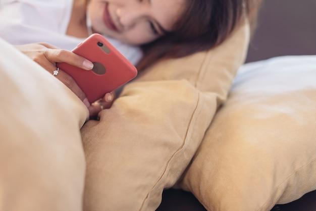 Femme asiatique à l'aide de smartphone à la maison le week-end.