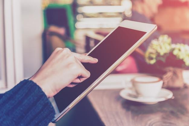 Femme asiatique à l'aide de tablette dans un café avec ton vintage.
