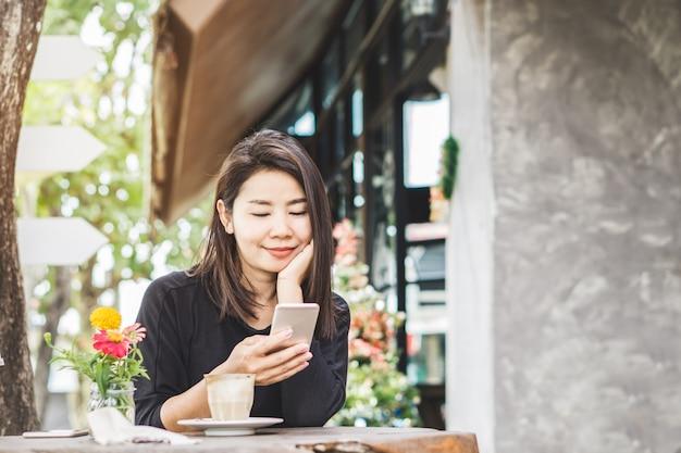 Femme asiatique à l'aide de téléphone intelligent et de boire du café