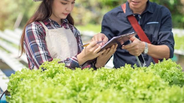 Une femme asiatique analyse et étudie la recherche sur les pots de légumes biologiques