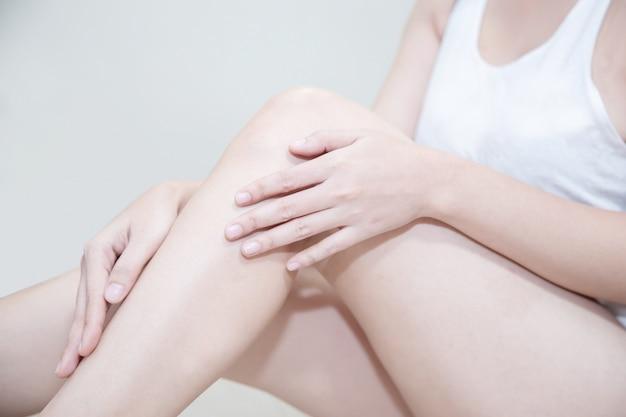 Femme asiatique, application, crème hydratante, sur, elle, jambe