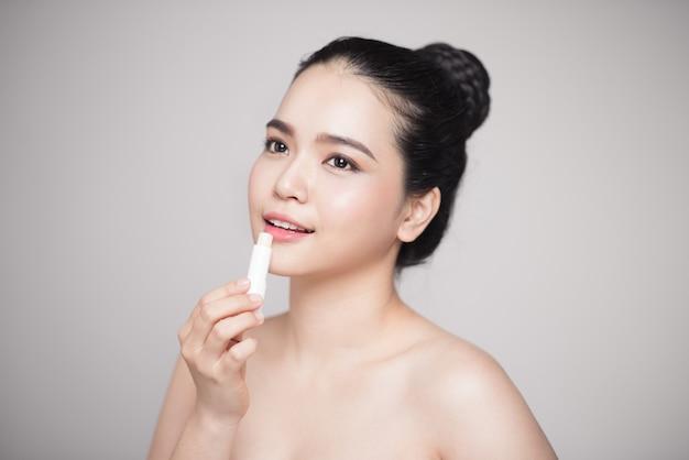 Femme asiatique appliquant un baume à lèvres hygiénique sur fond gris