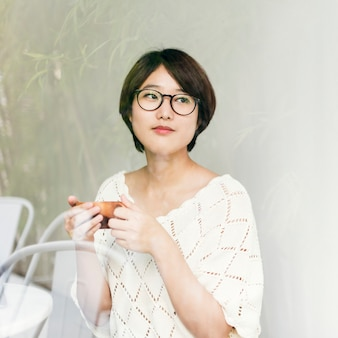 Une femme asiatique en appréciant sa tasse de thé