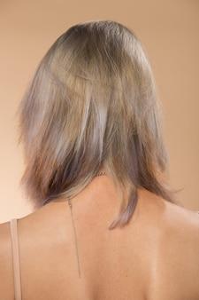 Femme asiatique après avoir appliqué le maquillage de cheveux gris argenté. pas de retouche, visage frais avec acné, lèvres, yeux. éclairage de studio fond jaune beige, pour traitement de thérapie esthétique, vue arrière arrière