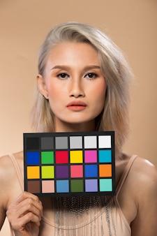 Femme asiatique après avoir appliqué le maquillage de cheveux gris argenté. pas de retouche, visage frais avec lèvres, yeux, joue, belle peau lisse. studio éclairage fond jaune beige, tenir le tableau de contrôle des couleurs
