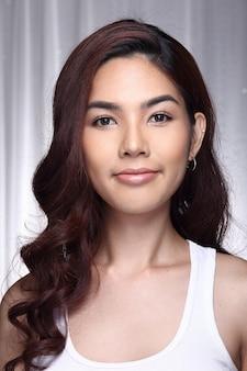 Femme asiatique après maquillage coiffure. pas de retouche, visage frais avec une peau agréable et lisse. studio éclairage fond gris
