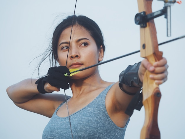Femme asiatique avec arc tir à l'arc