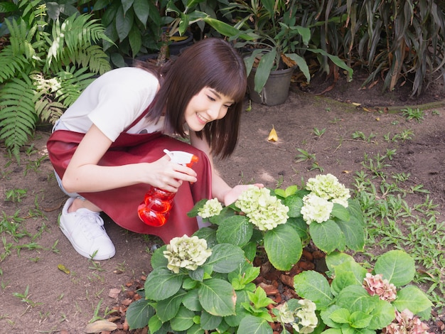 Femme asiatique arrosent des plantes
