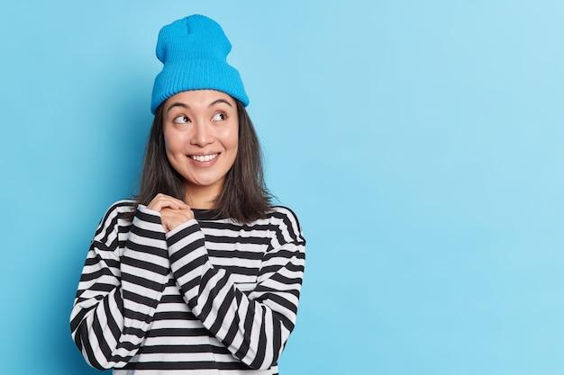 Une femme asiatique assez réfléchie garde les mains ensemble regarde de côté avec le sourire porte un chapeau et un pull rayé