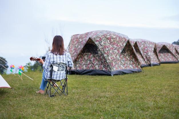 Femme asiatique assise sur une chaise de pique-nique et jouer de la guitare en camping en famille dans le camping dans la belle nature.