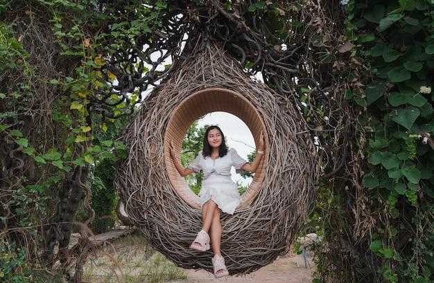Femme asiatique assise dans un nid d'oiseau en bois dans une forêt d'arbres verts à l'écart heureux de la nature