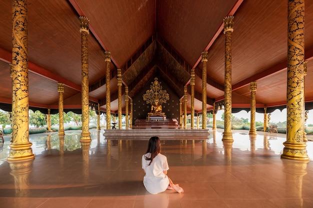 Femme asiatique assise méditation et statue de bouddha doré dans l'église bouddhiste de wat sirindhorn wararam