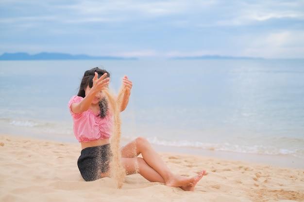 Femme asiatique assise sur la plage de sable à la mer de la côte. elle s'amuse pendant les vacances d'été.