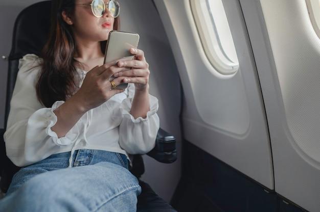Femme asiatique assise près de la fenêtre de l'avion et utilisant un téléphone portable pendant le vol