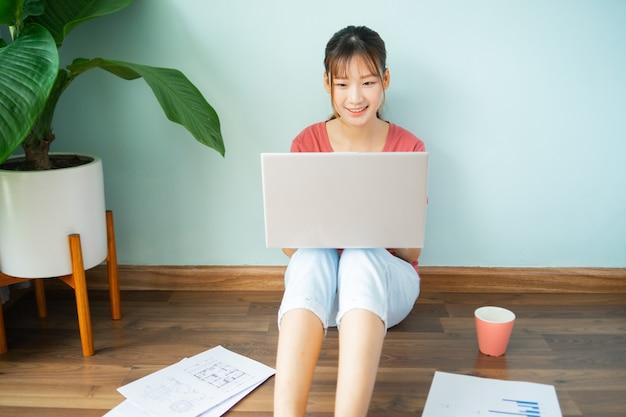 Femme asiatique assise sur le sol pendant qu'elle travaille à domicile